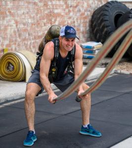 fitness member working on teh battle hoses